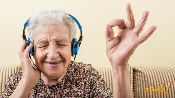 An elderly lady enjoys music through headphones