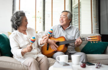 Couple playing music on guitar and maracas