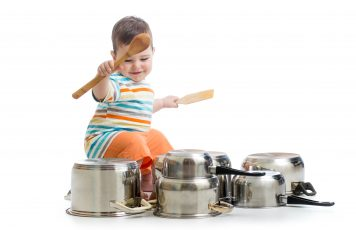 Baby plays pots & pans with wooden spoons