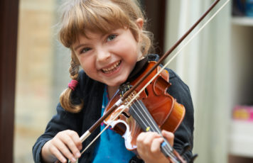 Young girl smiles while playing violin